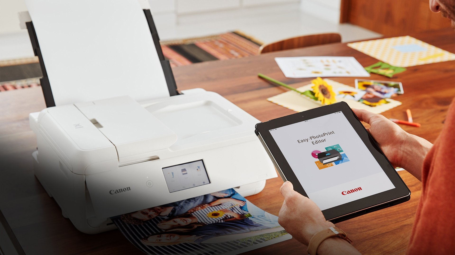 A person printing on a Canon PIXMA printer from a tablet using the Canon Easy-PhotoPrint Editor App.